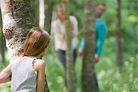 Girl playing hide and seek with parents in woods, rear view Stock Photo - Premium Royalty-Freenull, Code: 632-05845385