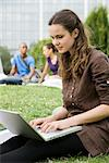 Young woman using laptop computer outdoors, people in background, portrait Stock Photo - Premium Royalty-Free, Artist: Uwe Umsttter, Code: 632-05845553