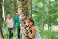 Girl hiding behind tree with finger on lips Stock Photo - Premium Royalty-Freenull, Code: 632-05845584