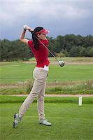 A female golfer teeing off Stock Photo - Premium Royalty-Freenull, Code: 653-05855436