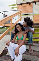 A young happy couple sitting on a staircase at the beach Stock Photo - Premium Royalty-Freenull, Code: 653-05855559
