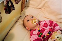 sucking - Baby in bed with comforter Stock Photo - Premium Royalty-Freenull, Code: 6108-05856057