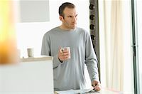 Man standing in the kitchen, holding mug Stock Photo - Premium Royalty-Freenull, Code: 6108-05856768
