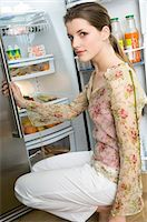 fridge - Woman crouching in front of refrigerator Stock Photo - Premium Royalty-Freenull, Code: 6108-05856940