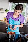 Woman cooking, using a garlic squeezer Stock Photo - Premium Royalty-Free, Artist: Photocuisine, Code: 6108-05857039