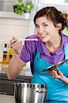 Young smiling woman tasting food Stock Photo - Premium Royalty-Free, Artist: Photocuisine, Code: 6108-05857041