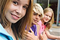 2 teenage girls and teenage boy smiling for camera Stock Photo - Premium Royalty-Freenull, Code: 6108-05857791
