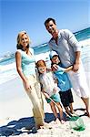 Parents and two children on the beach, posing for the camera, outdoors Stock Photo - Premium Royalty-Free, Artist: theblackrhino                 , Code: 6108-05858059