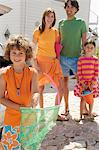 Parents and two children posing in front of house, holding beach accessories, outdoors Stock Photo - Premium Royalty-Free, Artist: Masterfile, Code: 6108-05858081