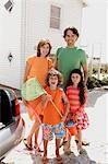 Parents and two children in front of a house, holding beach accessories, outdoors Stock Photo - Premium Royalty-Free, Artist: Masterfile, Code: 6108-05858099