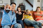 Parents and two teens holding eachothers a remote control, indoors Stock Photo - Premium Royalty-Freenull, Code: 6108-05858310