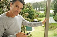 Man leaning against bay window, holding mobile phone Stock Photo - Premium Royalty-Freenull, Code: 6108-05858652