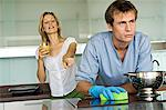 Smiling woman pointing at angry man holding sponge Stock Photo - Premium Royalty-Free, Artist: Blend Images, Code: 6108-05858959