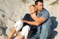 Couple embracing, sitting on the beach Stock Photo - Premium Royalty-Freenull, Code: 6108-05858963