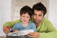 Father and son playing with model aeroplane Stock Photo - Premium Royalty-Freenull, Code: 6108-05859199