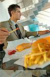 Mid adult businessman having burger and French fries, using laptop Stock Photo - Premium Royalty-Free, Artist: Jodi Pudge, Code: 6108-05859376