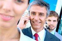 Business people using mobile phones, smiling Stock Photo - Premium Royalty-Freenull, Code: 6108-05859552