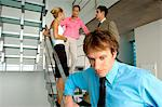 Businessman standing by staircase with colleagues in background Stock Photo - Premium Royalty-Free, Artist: CulturaRM, Code: 6108-05859603