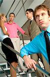 Businessman standing by staircase with colleagues in background Stock Photo - Premium Royalty-Free, Artist: Robert Harding Images, Code: 6108-05859612