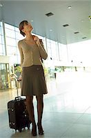 Businesswoman standing with her luggage at an airport lounge Stock Photo - Premium Royalty-Freenull, Code: 6108-05859698