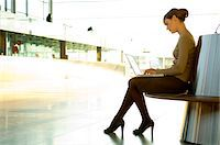 Side profile of a businesswoman using a laptop at an airport lounge Stock Photo - Premium Royalty-Freenull, Code: 6108-05859712
