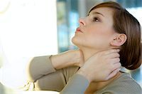 Close-up of a young woman with her hands on her neck Stock Photo - Premium Royalty-Freenull, Code: 6108-05859759