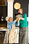 Young woman flipping a pancake with her son Stock Photo - Premium Royalty-Free, Artist: Photocuisine, Code: 6108-05859849