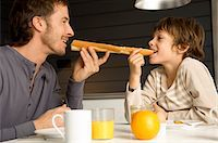 Mid adult man eating a baguette with his son Stock Photo - Premium Royalty-Freenull, Code: 6108-05859852
