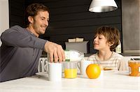 Mid adult man having breakfast with his son in the kitchen Stock Photo - Premium Royalty-Freenull, Code: 6108-05859875