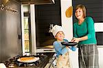 Young woman flipping a pancake with her son Stock Photo - Premium Royalty-Free, Artist: Photocuisine, Code: 6108-05859896