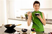 smelly - Mid adult woman smelling a bowl of rice in the kitchen Stock Photo - Premium Royalty-Freenull, Code: 6108-05859981