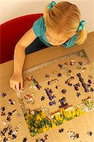 High angle view of a girl playing a jigsaw puzzle Stock Photo - Premium Royalty-Freenull, Code: 6108-05860227