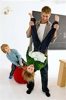 Mid adult man playing with his children Stock Photo - Premium Royalty-Freenull, Code: 6108-05860245
