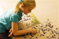 High angle view of a girl playing a jigsaw puzzle Stock Photo - Premium Royalty-Freenull, Code: 6108-05860256
