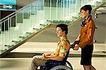Side profile of a female cabin crew pushing a mid adult man sitting in a wheelchair Stock Photo - Premium Royalty-Free, Artist: CulturaRM, Code: 6108-05860413