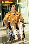 Mid adult man sitting in a wheelchair at an airport Stock Photo - Premium Royalty-Free, Artist: CulturaRM, Code: 6108-05860417