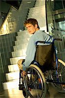 Mid adult man sitting in a wheelchair Stock Photo - Premium Royalty-Freenull, Code: 6108-05860423