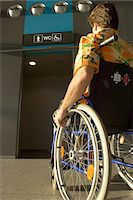 Rear view of a mid adult man sitting in a wheelchair Stock Photo - Premium Royalty-Freenull, Code: 6108-05860448
