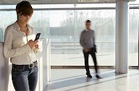 Businesswoman using a mobile phone with a businessman walking in the background Stock Photo - Premium Royalty-Freenull, Code: 6108-05860458