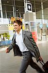 Side profile of a businessman rushing with his luggage at an airport Stock Photo - Premium Royalty-Free, Artist: Blend Images, Code: 6108-05860527
