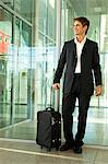 Businessman standing with his luggage at an airport Stock Photo - Premium Royalty-Free, Artist: Blend Images, Code: 6108-05860533