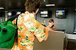 Female airline check-in attendant giving a passport and boarding pass to a passenger Stock Photo - Premium Royalty-Free, Artist: Michael Mahovlich, Code: 6108-05860569