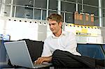 Businessman using a laptop at an airport lounge Stock Photo - Premium Royalty-Free, Artist: Blend Images, Code: 6108-05860584