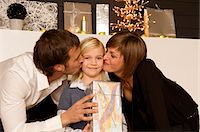 Young woman and a mid adult man kissing their daughter Stock Photo - Premium Royalty-Freenull, Code: 6108-05860618