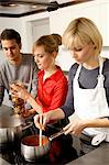 Two young women and a young man preparing food in the kitchen Stock Photo - Premium Royalty-Free, Artist: Photocuisine, Code: 6108-05861113
