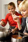 Two young women and a young man preparing food in the kitchen Stock Photo - Premium Royalty-Free, Artist: Photocuisine, Code: 6108-05861134