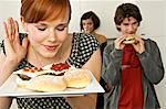 Young woman holding burgers in a tray with her friends in background Stock Photo - Premium Royalty-Free, Artist: Jodi Pudge, Code: 6108-05861155