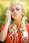 Young woman eating a yoghurt Stock Photo - Premium Royalty-Free, Artist: Photocuisine, Code: 6108-05861385