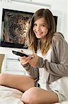 Portrait of a girl holding a remote control Stock Photo - Premium Royalty-Free, Artist: Andrew Kolb, Code: 6108-05862352