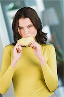sucking - Portrait of a woman sucking a slice of pineapple Stock Photo - Premium Royalty-Freenull, Code: 6108-05862414